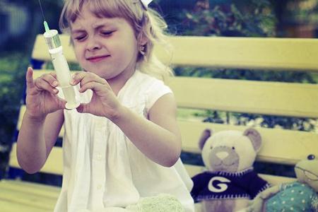 Девочка ставит укол игрушке