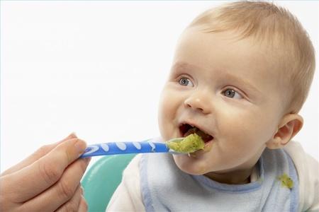 Ребёнка кормят с ложечки