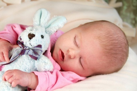Новорожденный спит с игрушкой