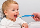 Ребёнка кормят кашей